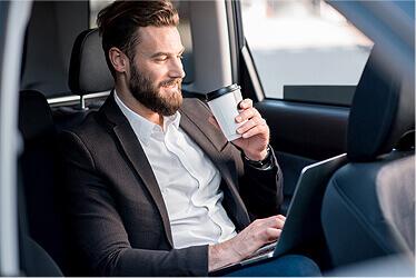 Ein Bild eines Mannes, der im Taxi Kaffee trinkt